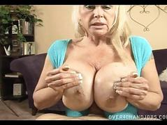 Tanned blonde momma with massive hooters doing titjob