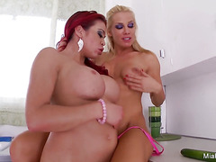 Two hot lesbians fuck each in the kitchen with cucumber