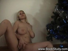 Busty girl masturbating by the Christmas tree